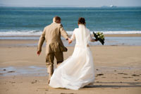 A Bride and groom walking on the beach